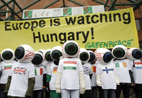 Greenpeace activists with eyeball-shaped helmets line up outside the Hungarian Foreign Ministry in Budapest